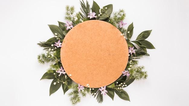 Okrągły papier na oddziałach zielonych roślin i kwiatów