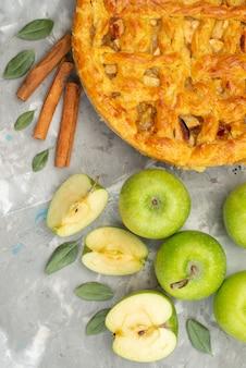 Okrągły placek jabłkowy z widokiem z góry tworzył pyszne ze świeżych jabłek i cynamonu na białym biurku ciasto herbatnikowe