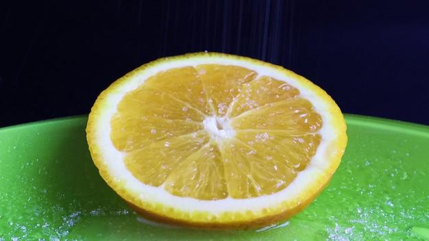 Okrągły plasterek pomarańczy, który wygląda bardzo soczyście i apetycznie posypany cukrem. zbliżenia cukru na świeżo pokrojony plasterek cytrusów na zielonej tablicy, na czarnym tle.