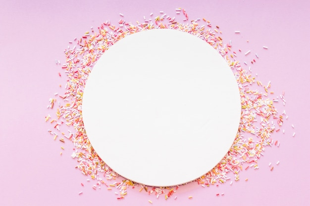 Okrągły pusty biały rama otoczona posypką na różowym tle