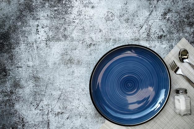 Okrągły pusty talerz ciemnoniebieski umieszczony w prawym dolnym rogu na stole betonowa czerń