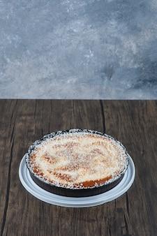 Okrągły pyszny tort umieszczony na drewnianym stole.