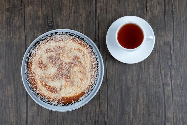 Okrągły pyszny tort z filiżanką herbaty postawiony na drewnianym stole.