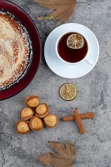Okrągły pyszny tort z filiżanką herbaty postawiony na marmurowym stole.