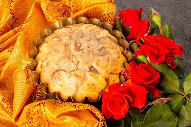 Okrągły słodki tort z widokiem z góry pyszne i pyszne ciasto czekoladowe wewnątrz patelni do ciasta wraz z czerwonymi różami na szarym tle herbatniki cukrowe