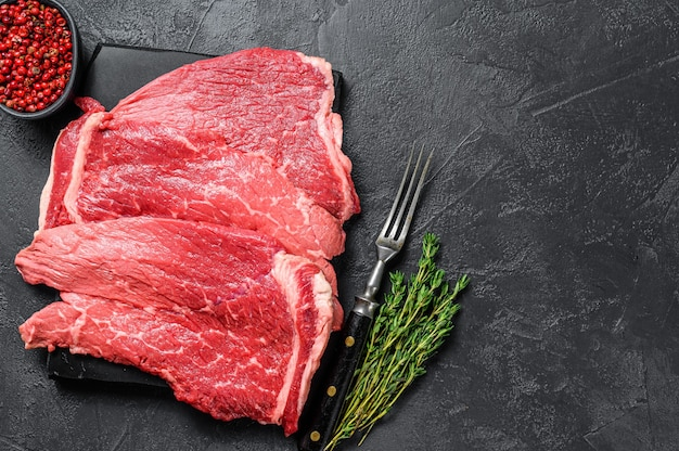 Okrągły stek wołowy surowego mięsa na pokładzie marmuru. czarne tło. widok z góry. skopiuj miejsce.