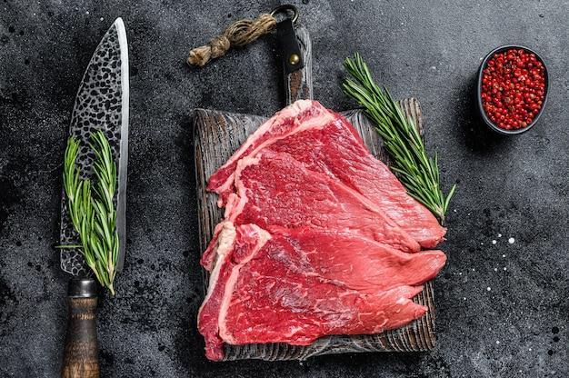 Okrągły stek z surowego świeżego mięsa wołowego z ziołami i przyprawami. czarne tło. widok z góry.