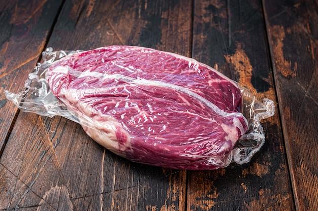 Okrągły stek z surowej, suchej sezonowanej wołowiny. ciemne drewniane tło. widok z góry.