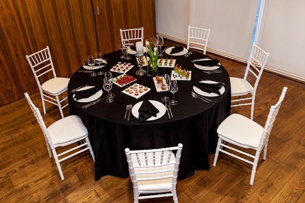Okrągły stół z czarnym obrusem i czarnymi serwetkami komplet sztućców z przekąskami na bankiet