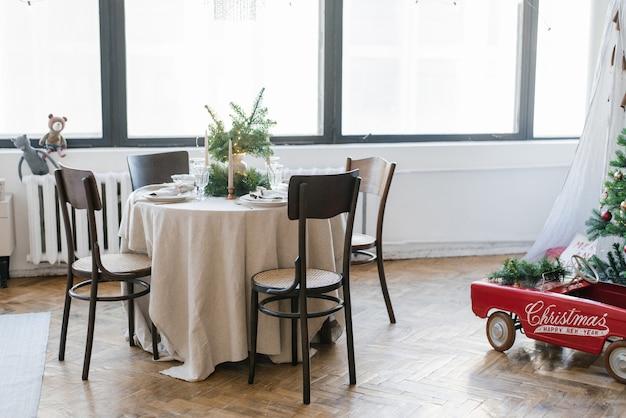 Okrągły stół z drewnianymi krzesłami udekorowany na świąteczny rodzinny obiad wnętrze salonu