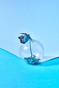 Okrągły szklany wazon z niebieskimi płatkami na spodzie i suszonym kwiatem róży
