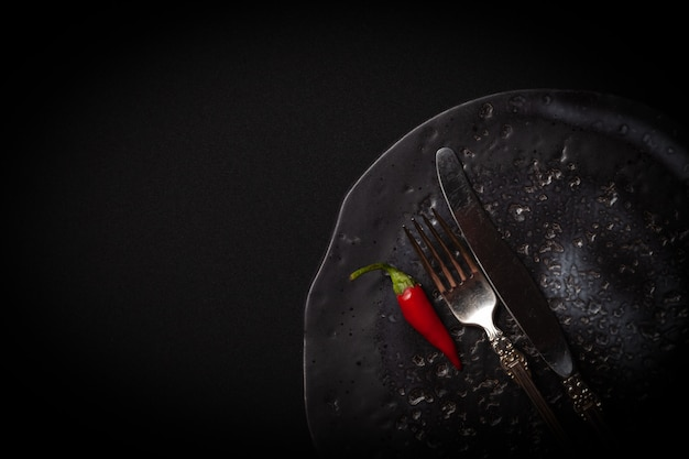 Okrągły talerz ceramiczny, vintage widelec, nóż czerwona świeża papryka chili na czarnym tle