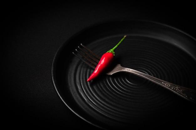 Okrągły talerz ceramiczny z wzorem, vintage widelec, czerwona świeża papryka chili na czarnym tle