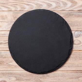 Okrągły talerz na stole. czarne naczynie na drewniane tła. kopia przestrzeń