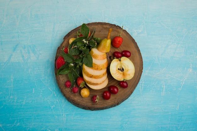 Okrągły talerz owoców z gruszkami, jabłkiem i jagodami na środku