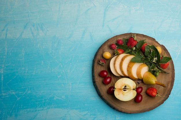 Okrągły talerz owoców z gruszkami, jabłkiem i jagodami