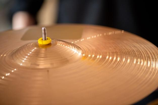Okrągły talerz w złotym kolorze jako część zestawu perkusyjnego współczesnego perkusisty lub innego muzyka i może służyć jako tło