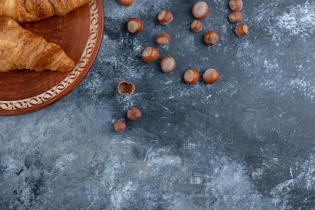 Okrągły talerz ze świeżymi rogalikami i zdrowymi orzechami makadamia.