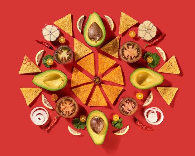 Okrągły tradycyjny meksykański wzór z chipsami nachos kukurydzianych, świeżymi naturalnymi owocami, warzywami, przyprawami, zieleniną chilli - składniki do dressingu guacamole na czerwonym tle. leżał na płasko.