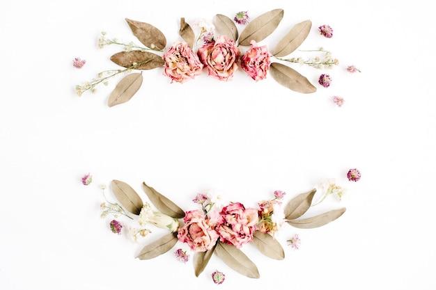 Okrągły wieniec z róż, różowe pąki kwiatowe, gałęzie i suszone liście na białym tle na białej powierzchni
