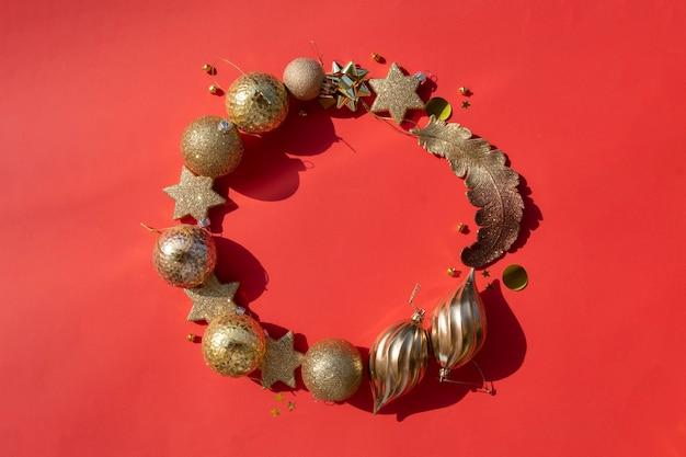 Okrągły wieniec ze złotych ozdób choinkowych na czerwonym tle idealny szablon do twojego projektu bożonarodzeniowego
