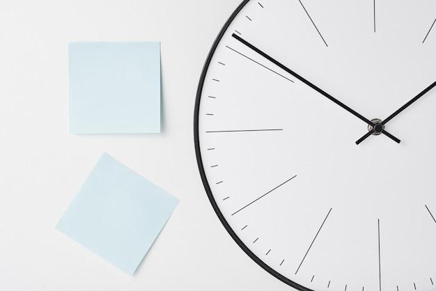 Okrągły zegar ścienny i niebieskie naklejki na białym tle