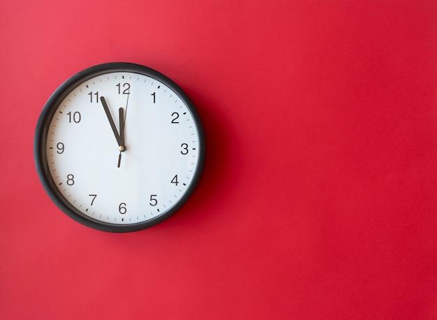 Okrągły zegar ścienny na czerwonej powierzchni pokazujący 12