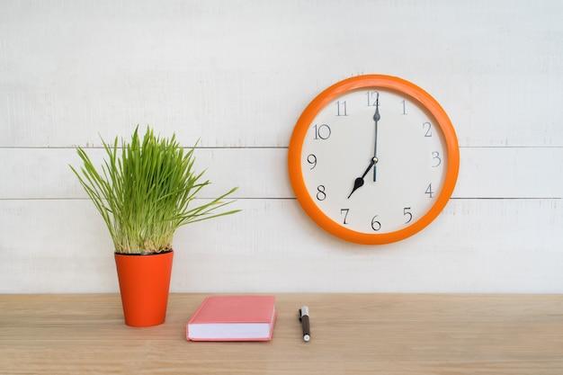 Okrągły zegar ścienny, różowy notatnik na stole i zielona roślina doniczkowa. miejsce pracy. początek dnia pracy