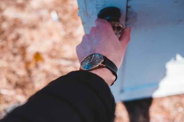Okrągły zegarek analogowy w złotym kolorze z czarnym skórzanym paskiem
