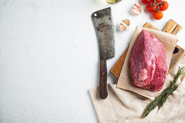 Okrągły zestaw surowego mięsa wołowego, na drewnianej desce do krojenia ze starym nożem tasakowym, widok z góry na płasko