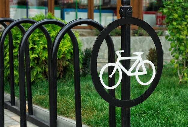 Okrągły znak z białym rowerem. parking jest pusty