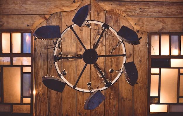 Okrągły żyrandol ze starych żelazek na tle drewnianego sufitu z oknami, widok z dołu