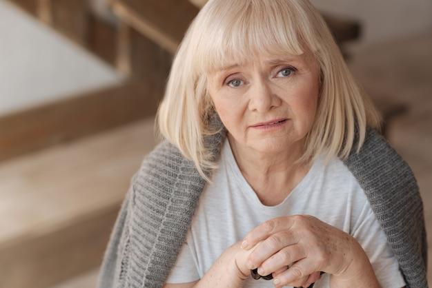 Okres depresji. portret zdenerwowanej, przygnębionej kobiety w wieku trzymającej kij i patrząc na ciebie, będąc nieszczęśliwym