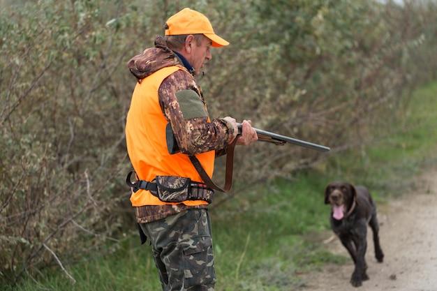 Okres polowań, sezon jesienny otwarty. myśliwy z bronią w ręku w stroju myśliwskim w jesiennym lesie w poszukiwaniu trofeum. mężczyzna stoi z bronią i psami myśliwskimi tropiącymi zwierzynę.
