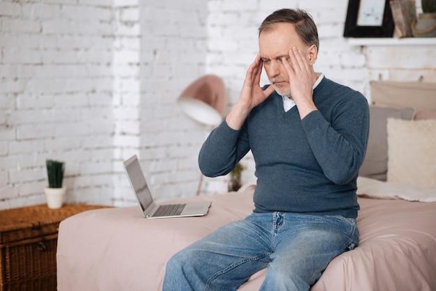 Okropna migrena. portret starego przystojnego mężczyzny, który dotyka jego skroni z powodu strasznego bólu głowy, siedząc na łóżku.
