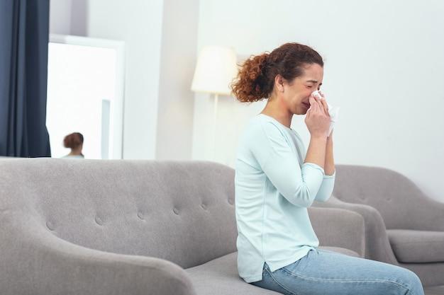 Okropnie chory. młoda, kręcona dziewczyna siedząca na szarej kanapie znowu kicha i wdmuchuje nos w papierową chusteczkę, cierpiąc na przeziębienie