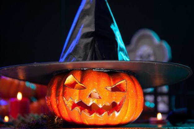 Okrutne pompowanie z przerażającą twarzą w kapeluszu wiedźmy na imprezie halloweenowej. dynia pomarańczowa. halloweenowa dekoracja.