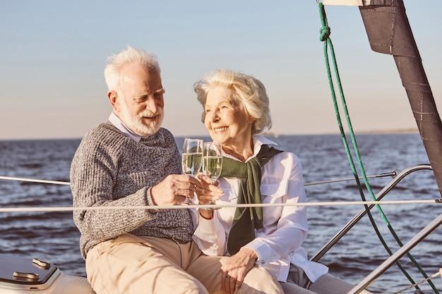 Okrzyki z bliska szczęśliwej pary seniorów siedzącej z boku żaglówki lub pokładu jachtu unoszącego się w wodzie