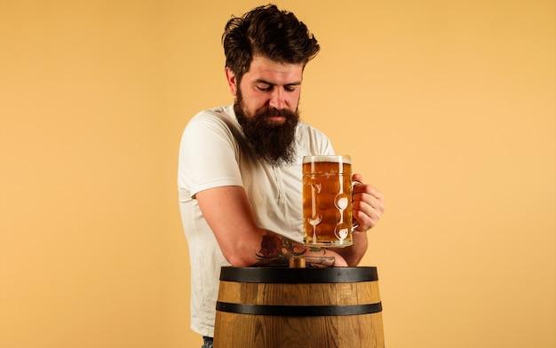Oktoberfest. brodaty mężczyzna pije piwo rzemieślnicze. facet ze szklanym pysznym piwem. pub i bar. piwowar. alkohol