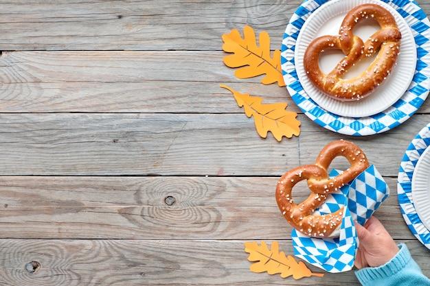 Oktoberfest, precle na jednorazowych talerzach, ręka trzymająca precel i jesienne liście z kopią