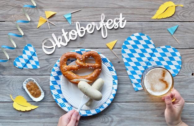 Oktoberfest, tradycyjne festiwalowe jedzenie: białe kiełbaski, precel i piwo. mieszkanie leżało na rustykalnym drewnianym stole z niebiesko-białymi kratkami i żółtymi jesiennymi liśćmi