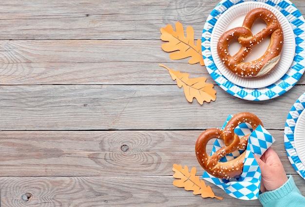 Oktoberfest, żeński ręka trzyma precla, miejsce na drewnianym stole