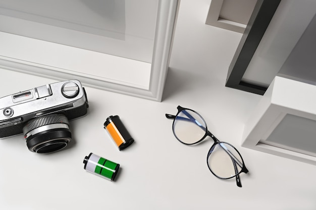 Okulary, aparat i ramka na zdjęcia na białym tle.