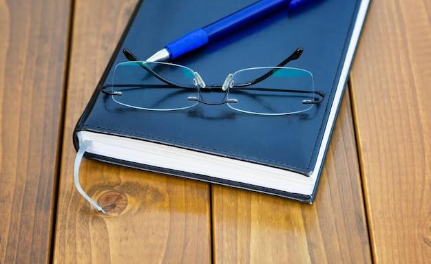 Okulary bez oprawek długopis na drewnianym stolezbliżenie
