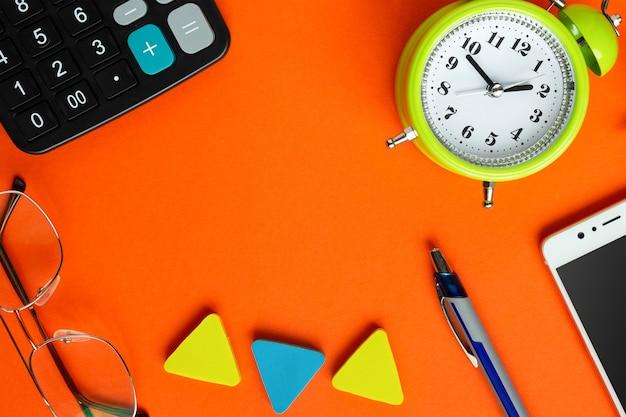 Okulary, budzik, smartfon, kalkulator i długopis na jasnopomarańczowym stole.