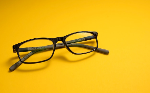 Okulary dla dzieci leżą na żółtym zbliżeniu z miejscem na tekst. kopiuj miejsce. pojęcie krótkowzroczności u dzieci, astygmatyzmu, problemów ze wzrokiem, wad wzroku.
