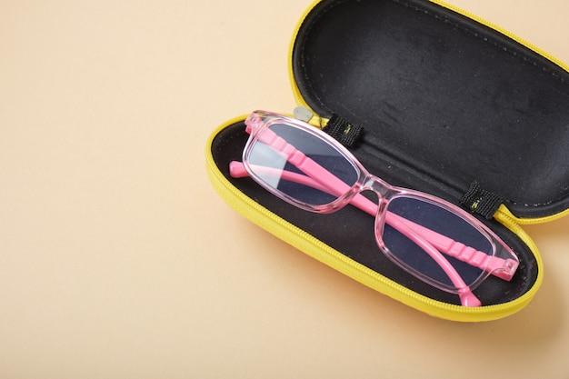 Okulary dla dzieci w etui na beżowym tle