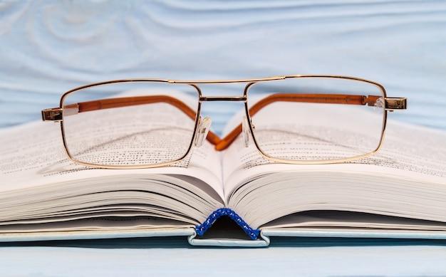 Okulary do czytania leżą na otwartej książce z bliska