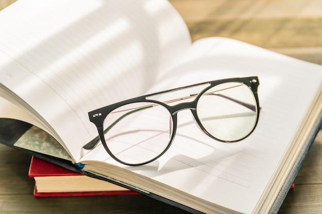 Okulary do czytania założyć na otwartą książkę na drewnianym stole