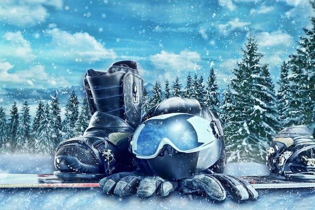 Okulary do sportów zimowych, narty, kask i rękawice w zimowym lesie